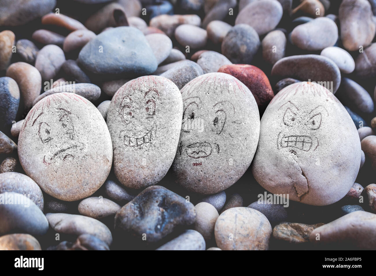 managing emotions emoji faces on stones - sad, happy, surprised worried and angry feelings draw Stock Photo