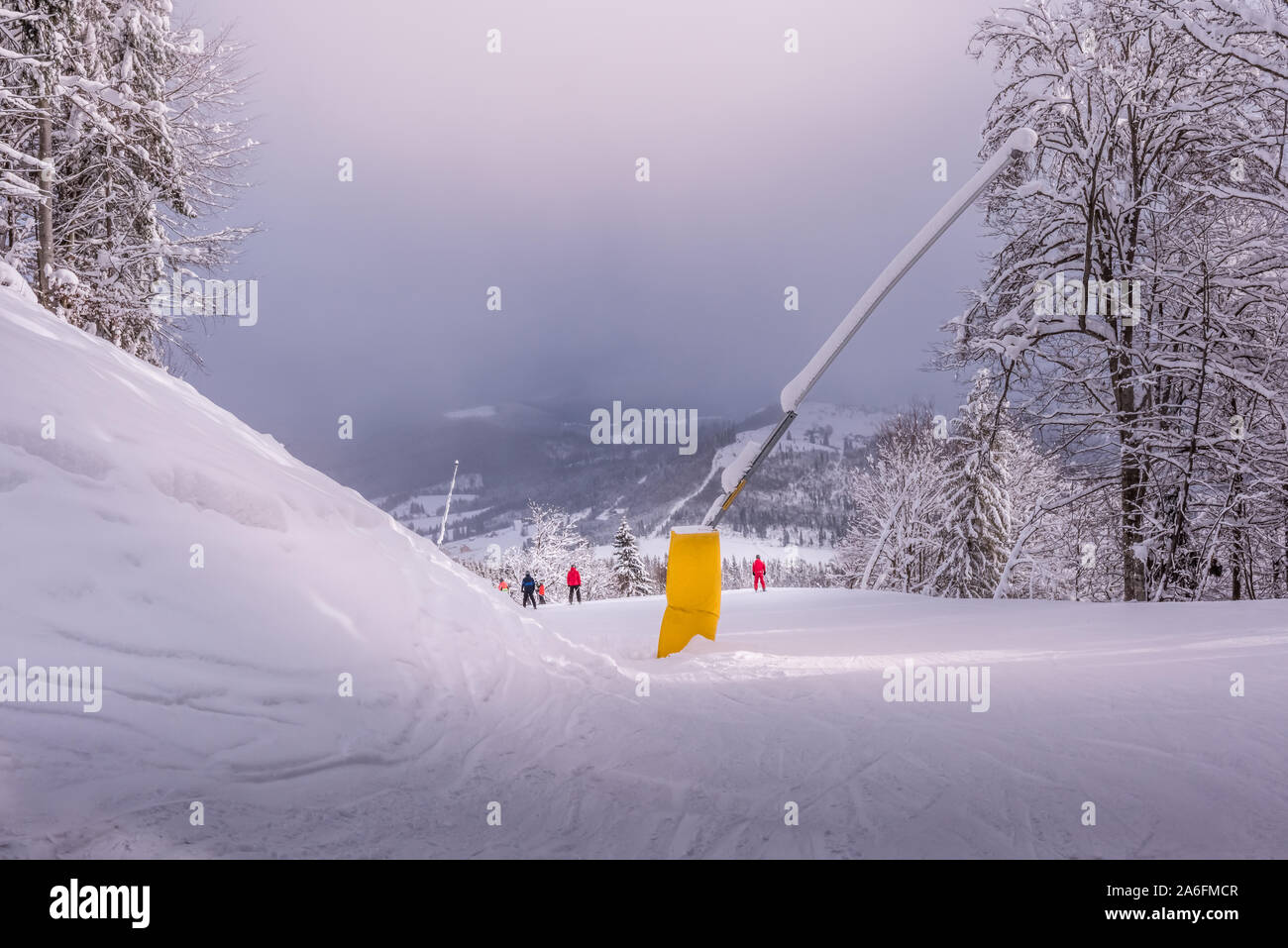 Bukovel ski resort slope with snow blowers and with few unidentifiable hobby skiers in red. Foggy weather at Carpathian mountains ski resort in Ukrain Stock Photo