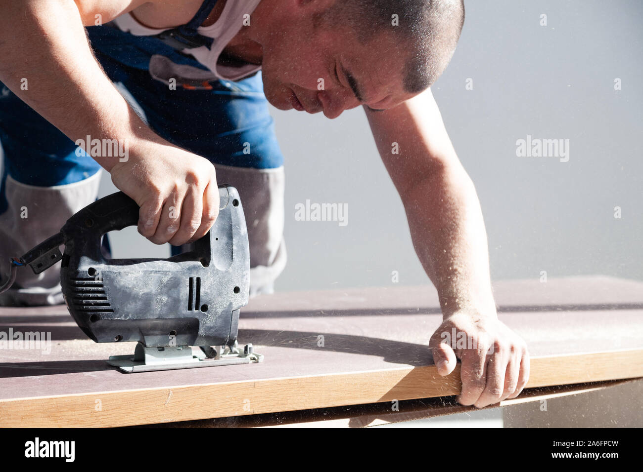 Closeup hand of carpenter, woodworker with professional cutting tool fretsaw or jigsaw, cut wooden tabletop, sawing plank, brown filings, sawdust. Con Stock Photo
