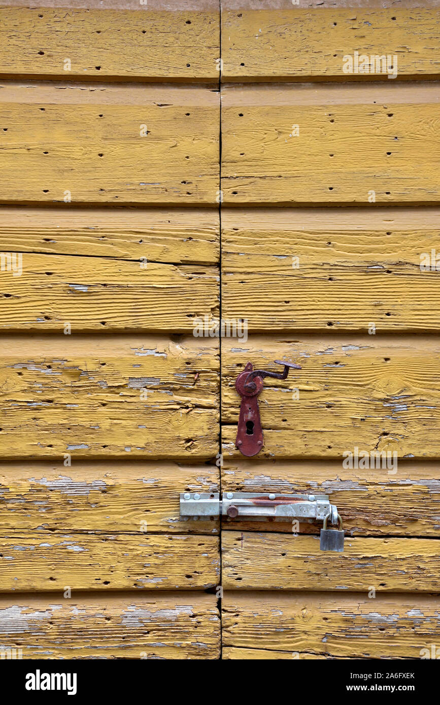 Old wooden doors with flacking paint, slide bolt and keyhole for lock Stock Photo