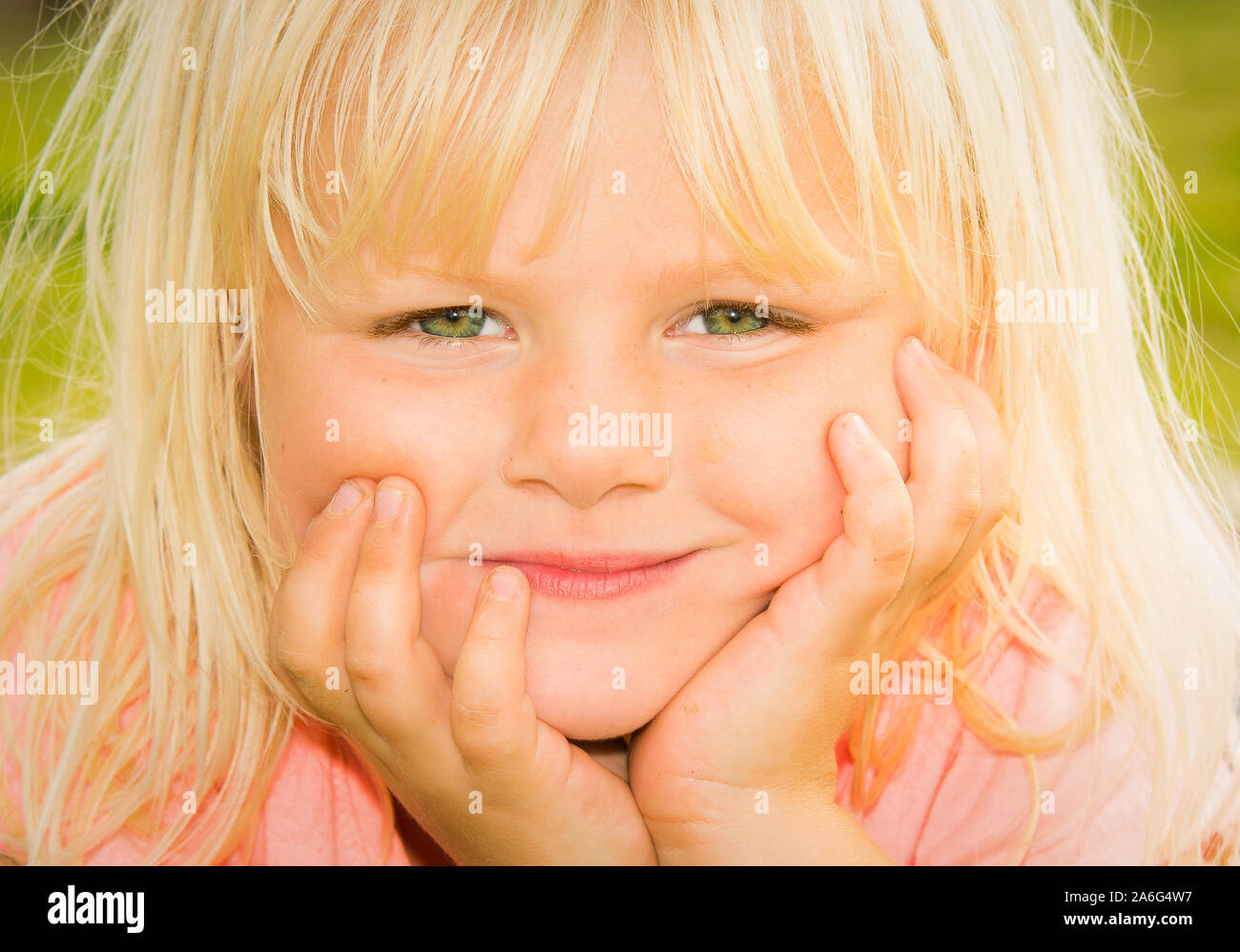 A Pretty Little Girl With Blonde Hair And Bright Green Eyes Lying