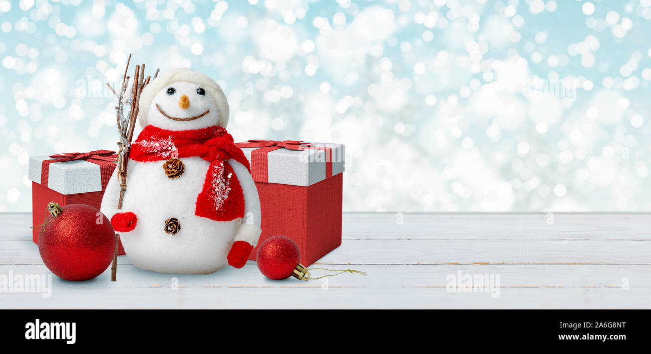 christmas background with snowman gifts and balls on wooden table free space beside for greeting text 2A6G8NT