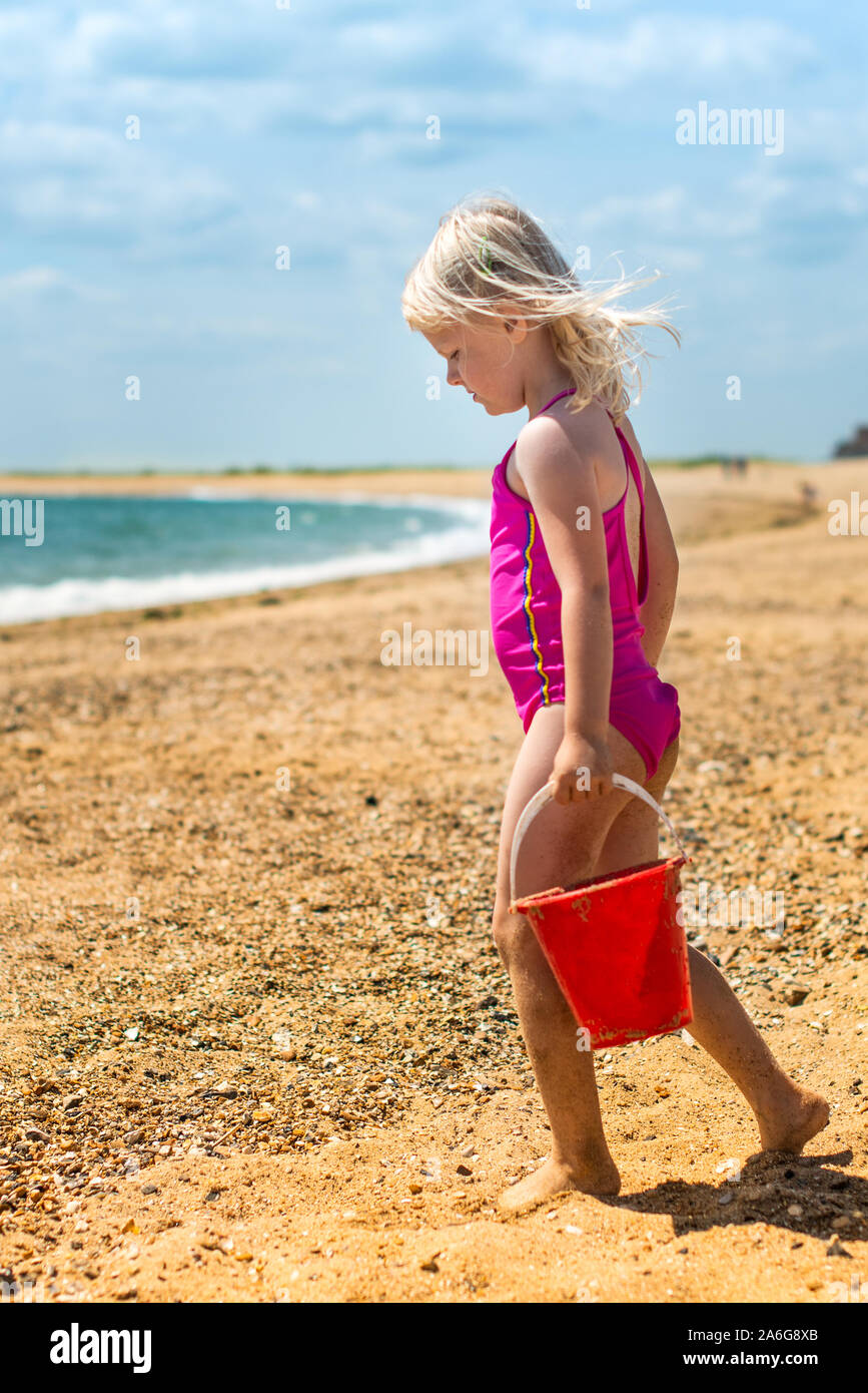 A cute, pretty little girl carrying a red bucket walking on the beach towards the sea, Stock Photo