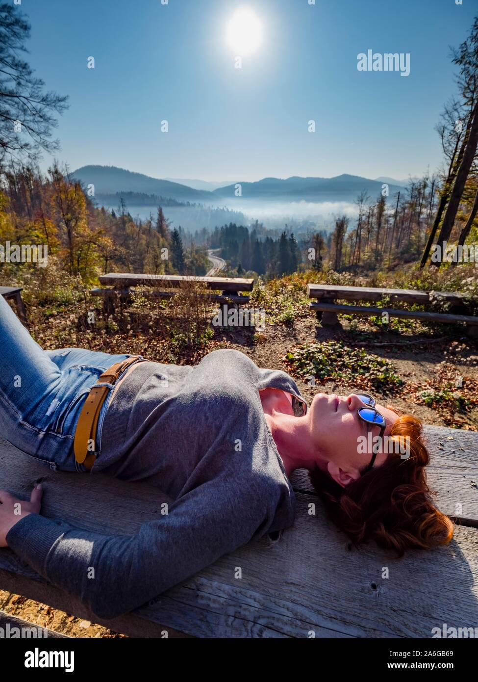 Fit woman laing on back on wooden bench against sun sunlight sunshine in nature Stock Photo