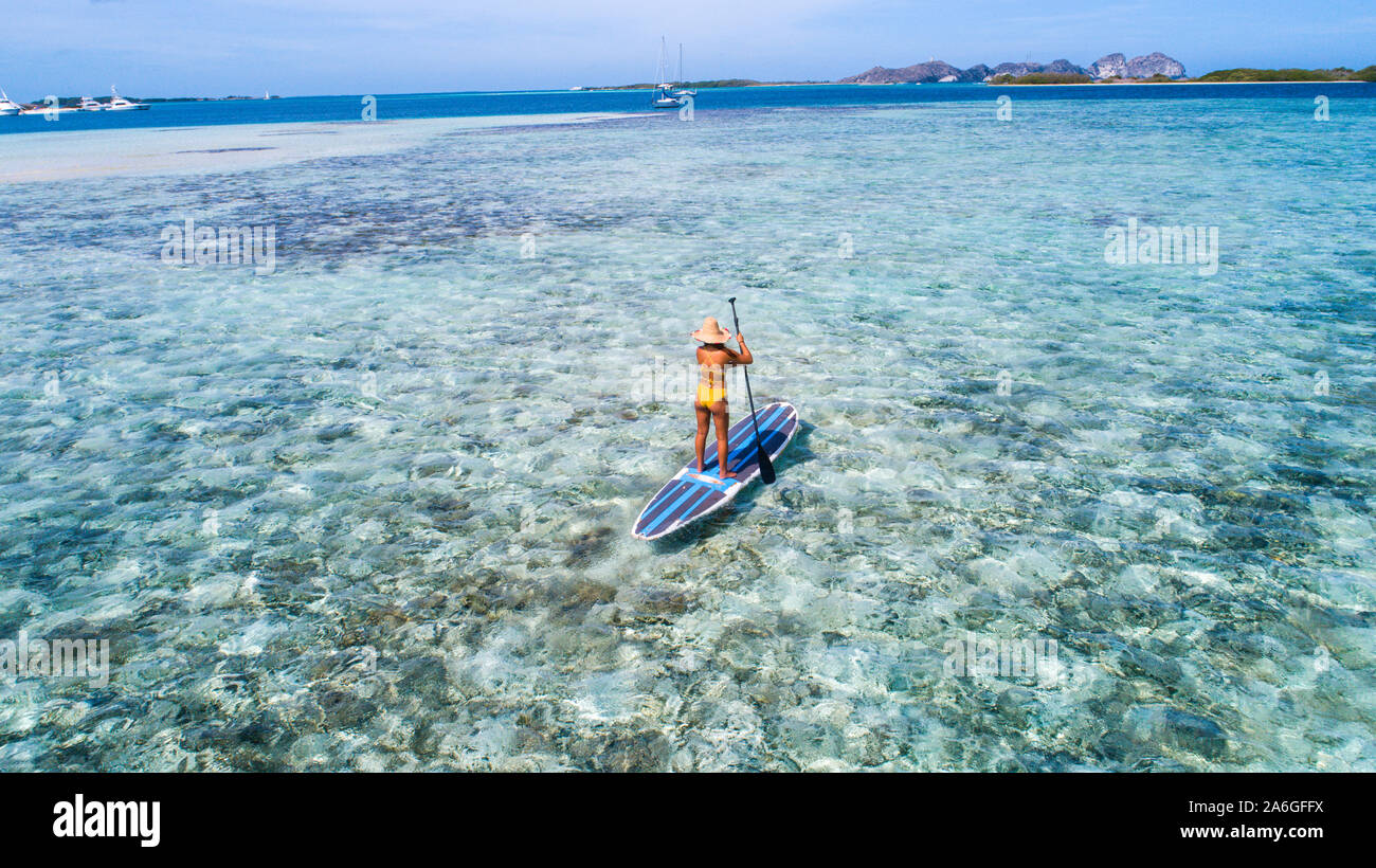 Aerial drone bird's eye view photo of young woman practising paddle board or sup in tropical Caribbean sapphire crystal clear calm waters Stock Photo