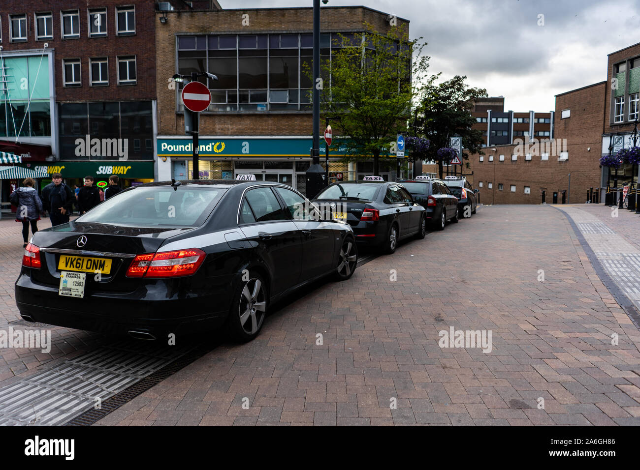 A selection of Taxi's, cabs wait for customers on the high street Stock Photo