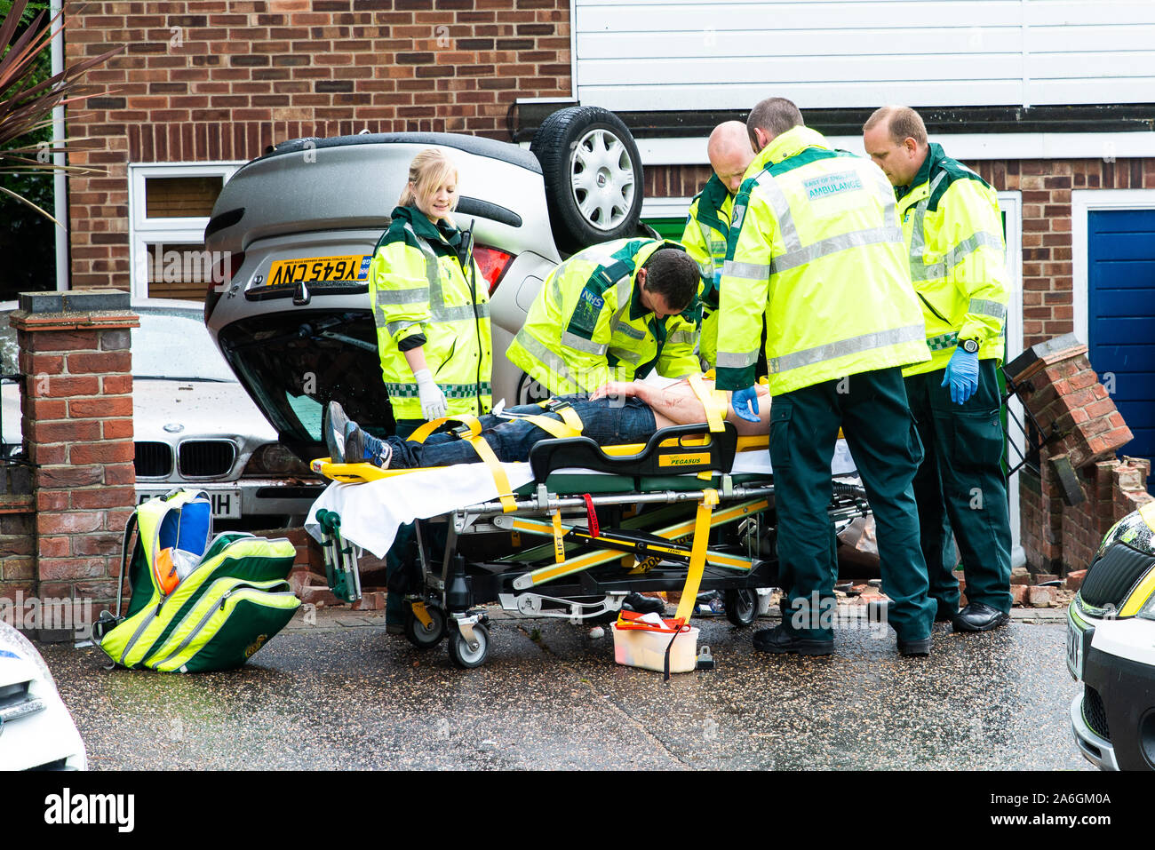 Emergency services on scene at a drink driving accident with an over turned and injured driver, Police, ambulance paramedics and fire brigade, Police Stock Photo