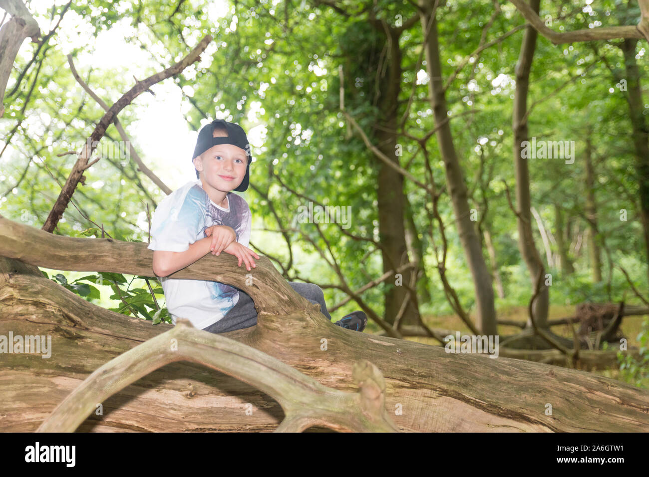 A cheeky little boy sitting in a cornfield wearing a baseball cap, while out playing with friends Stock Photo