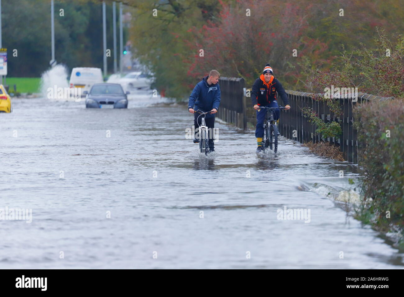 Cyclists battle through floodwater in Castleford after 24 hours of rainfall Stock Photo