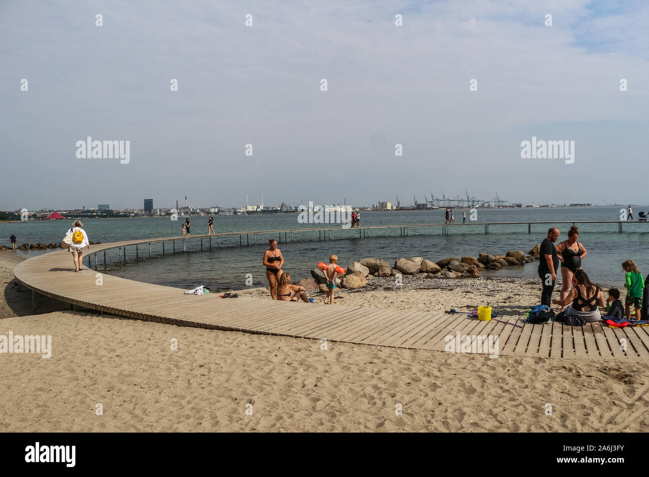 People walking by the The Infinite Bridge (Den Uendelige Bro) - circle shaped wooden pier built on a sea coast of a Aarhus Bay on a Varna Beach/Ballehage Beach, created by architect Niels Povlsgaard and Johan Gjødes  are seen in Aarhus, Denmark on 30 July 2019  © Michal Fludra / Alamy Live News Stock Photo