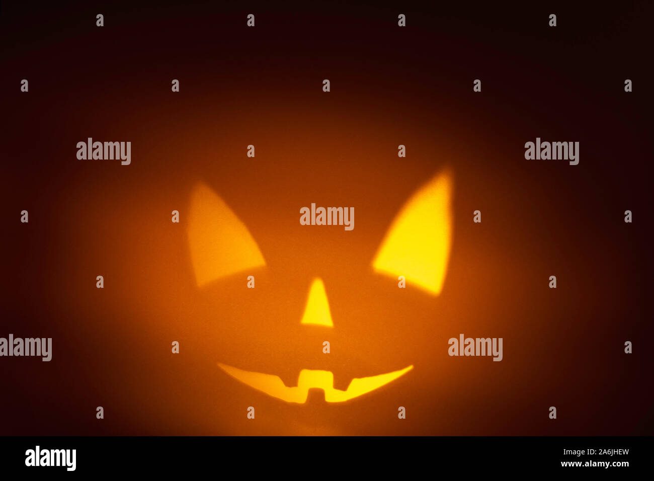 Character halloween scary pumpkin face on dark orange paper background. Scary smile face. Halloween horror background Stock Photo