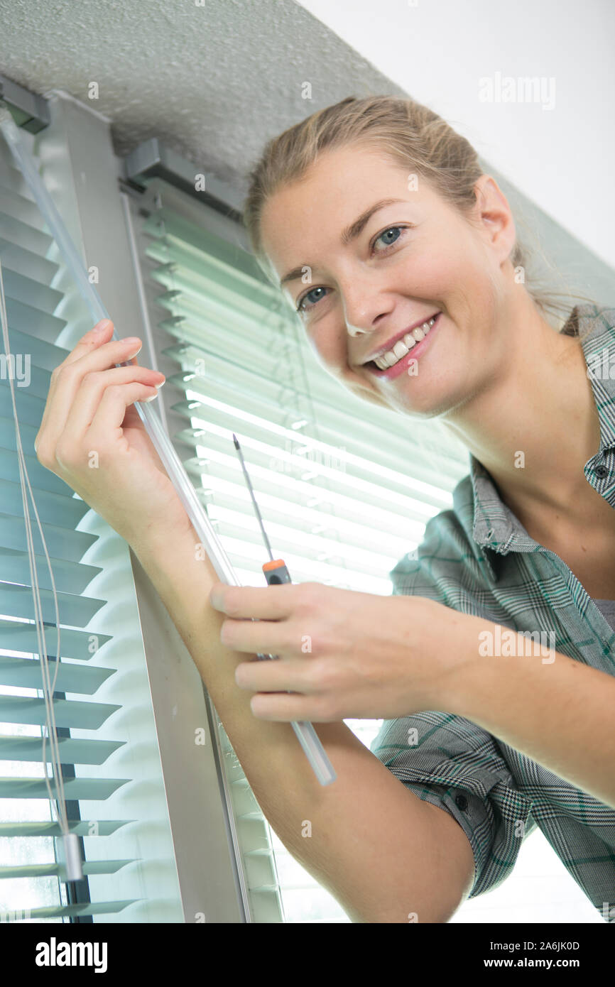 woman adjusting window blind Stock Photo