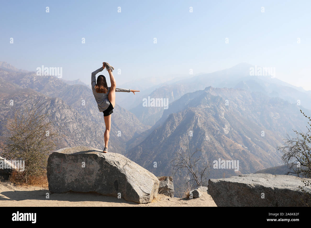 Young female engages in incredible yoga pose in scenic mountain setting. Stock Photo