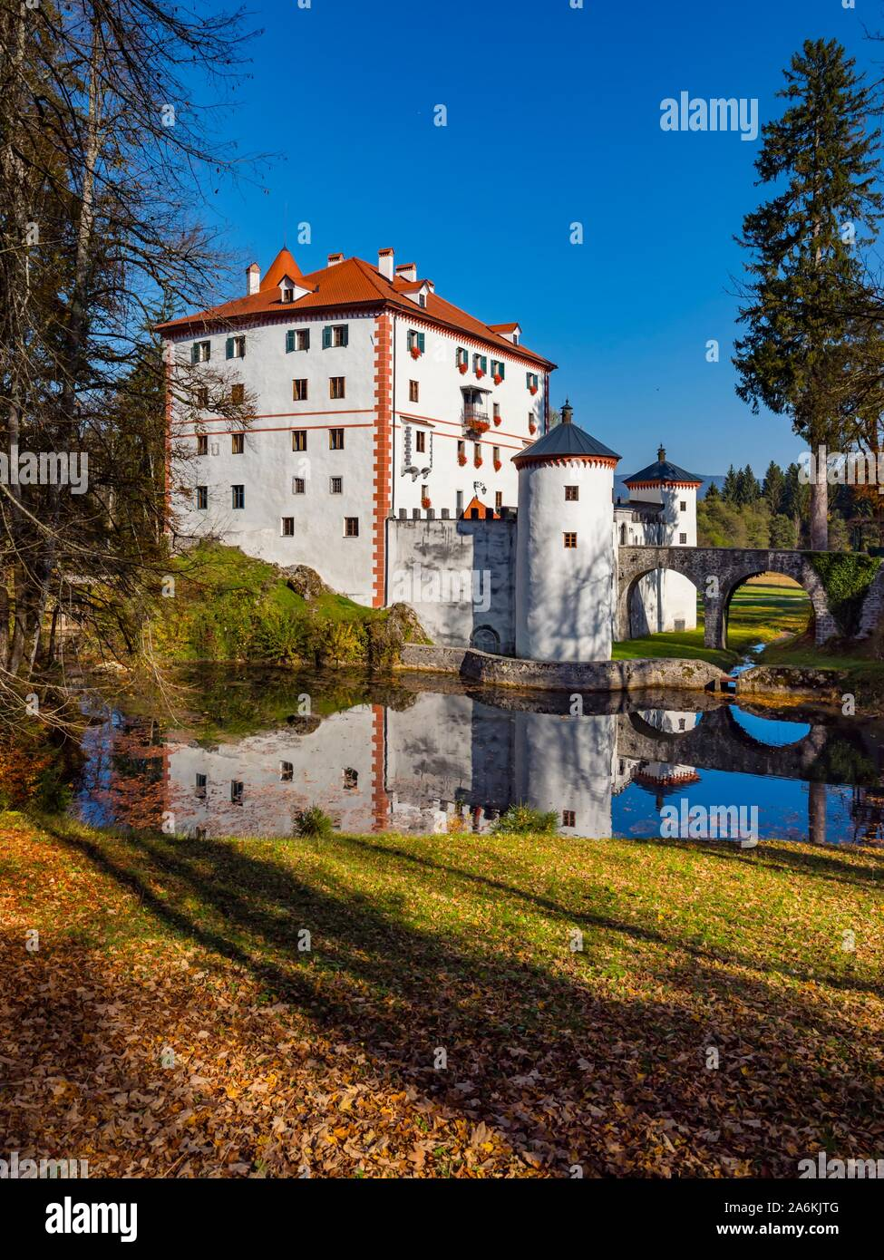 Sneznik castle in Slovenia forest trees vegetation calm reflection mirror image peaceful quiet lake Stock Photo