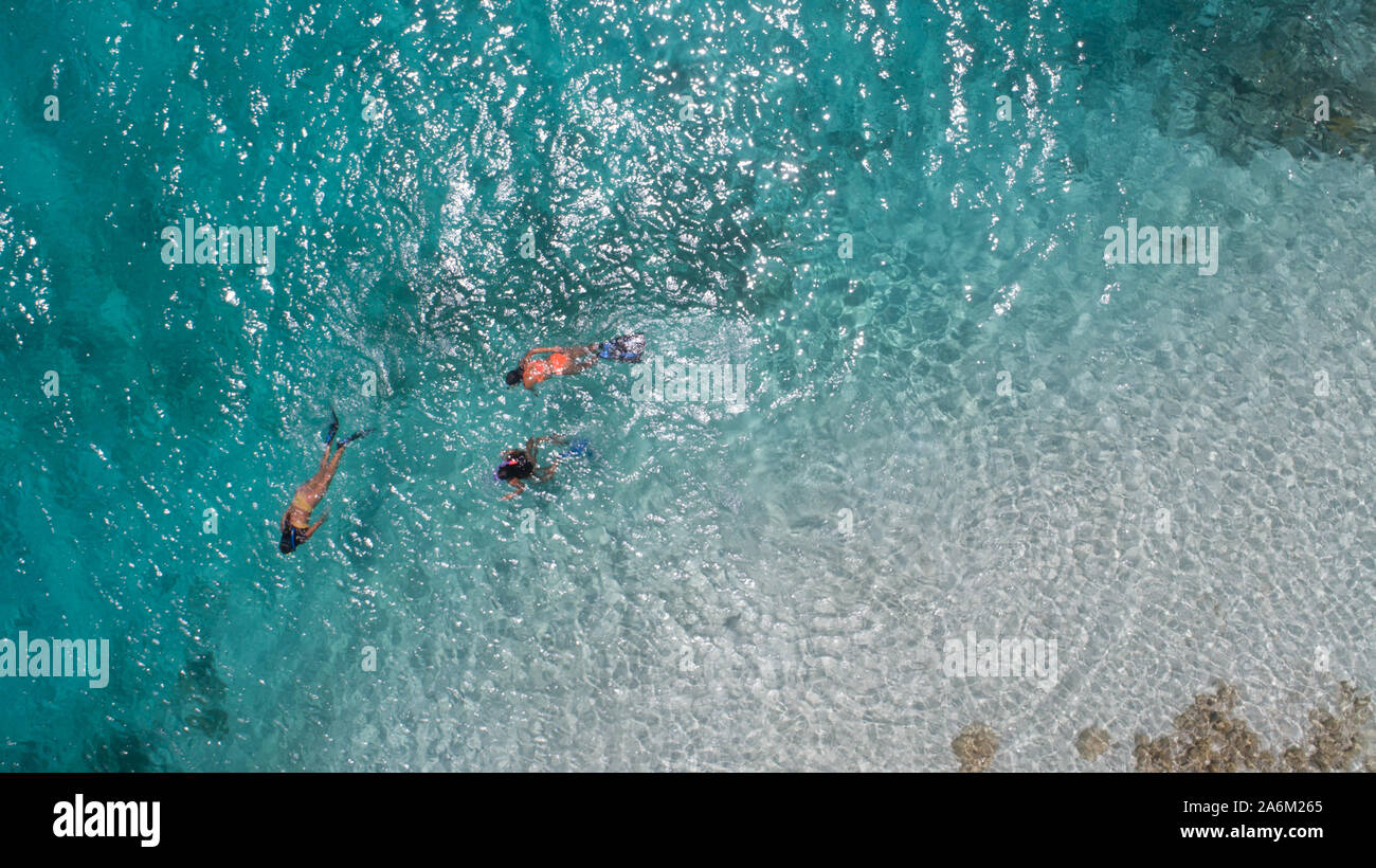 Three young girls snorkeling in blue waters above coral reef  in tropical Caribbean sapphire crystal clear calm waters  People and lifestyle concept Stock Photo