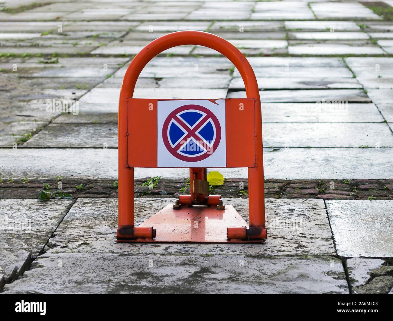 Portable road sign no stopping or parking on an orange car parking lock device over wet concrete slabs near building. Traffic rules,  prohibitory sign Stock Photo