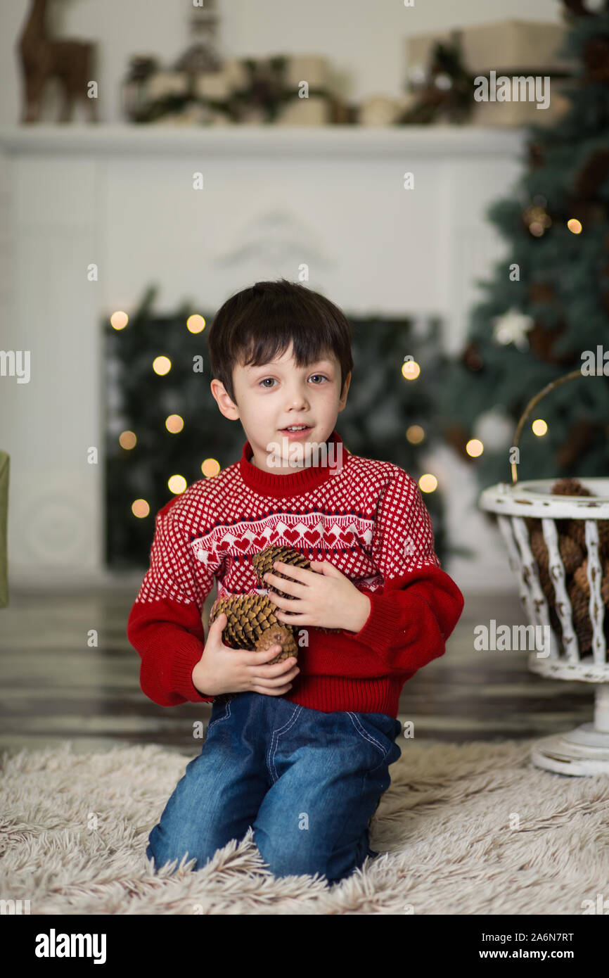 Christmas Plays Near Me 2020 Portrait of a little boy play with pine cones near a Christmas