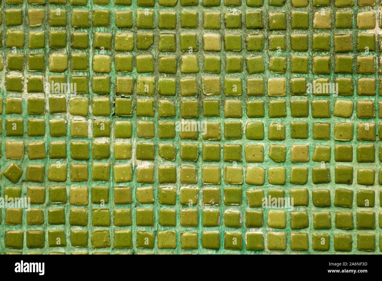 Background texture of old handmade green / turquoise mixture multi-colored ceramic mosaic tiles with space between them. Stock Photo