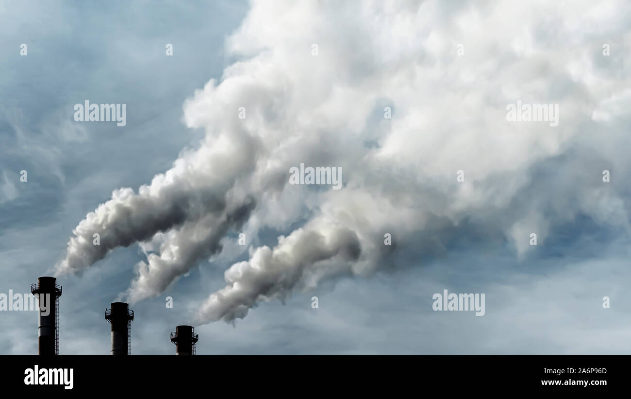 Toxic emissions of toxic gases into the atmosphere, industrial air pollution. Dark chimneys blowing huge billows of smoke into the sky Stock Photo