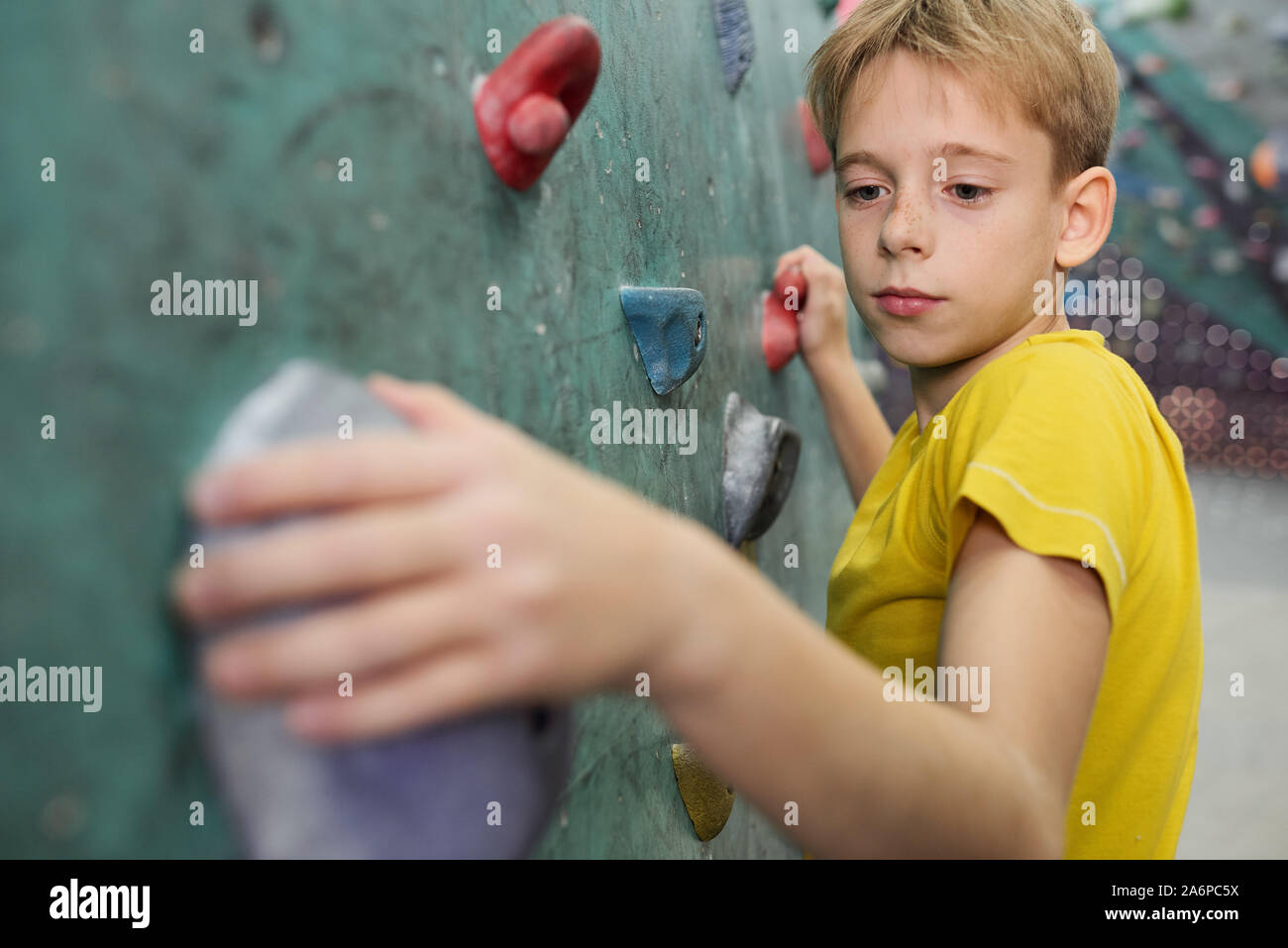 Young schoolboy in yellow t-shirt holding by small rocks on climbing wall Stock Photo