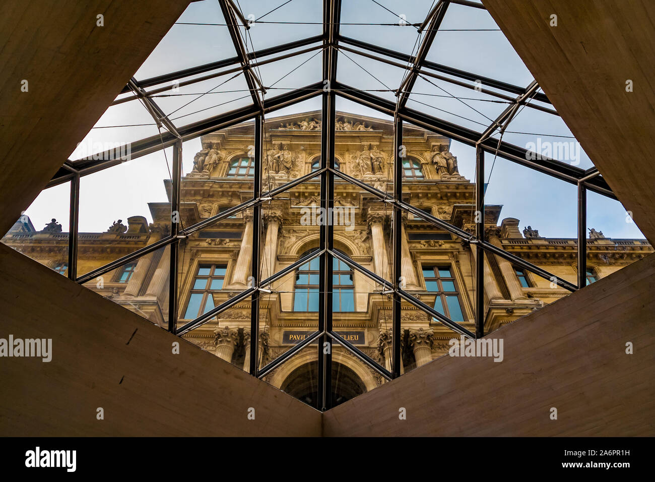 Artistic view of the beautiful façade of the Richelieu Wing through a diamond shaped opening, covered with the glass panes of the Louvre Pyramid in... Stock Photo