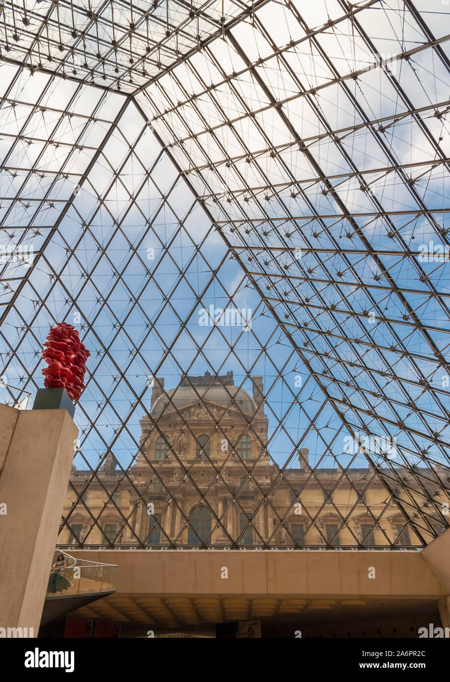 Great portrait view of the Richelieu Wing through the glass of the Louvre Pyramid in Paris from the underground lobby with the red sculpture Versus of... Stock Photo