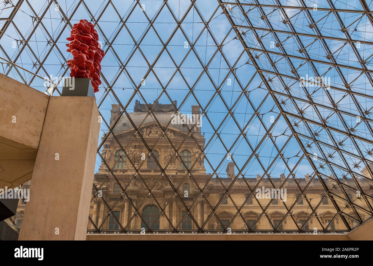 Special view of the Richelieu Wing through the glass of the Louvre Pyramid in Paris from the underground lobby of the museum with the red sculpture... Stock Photo