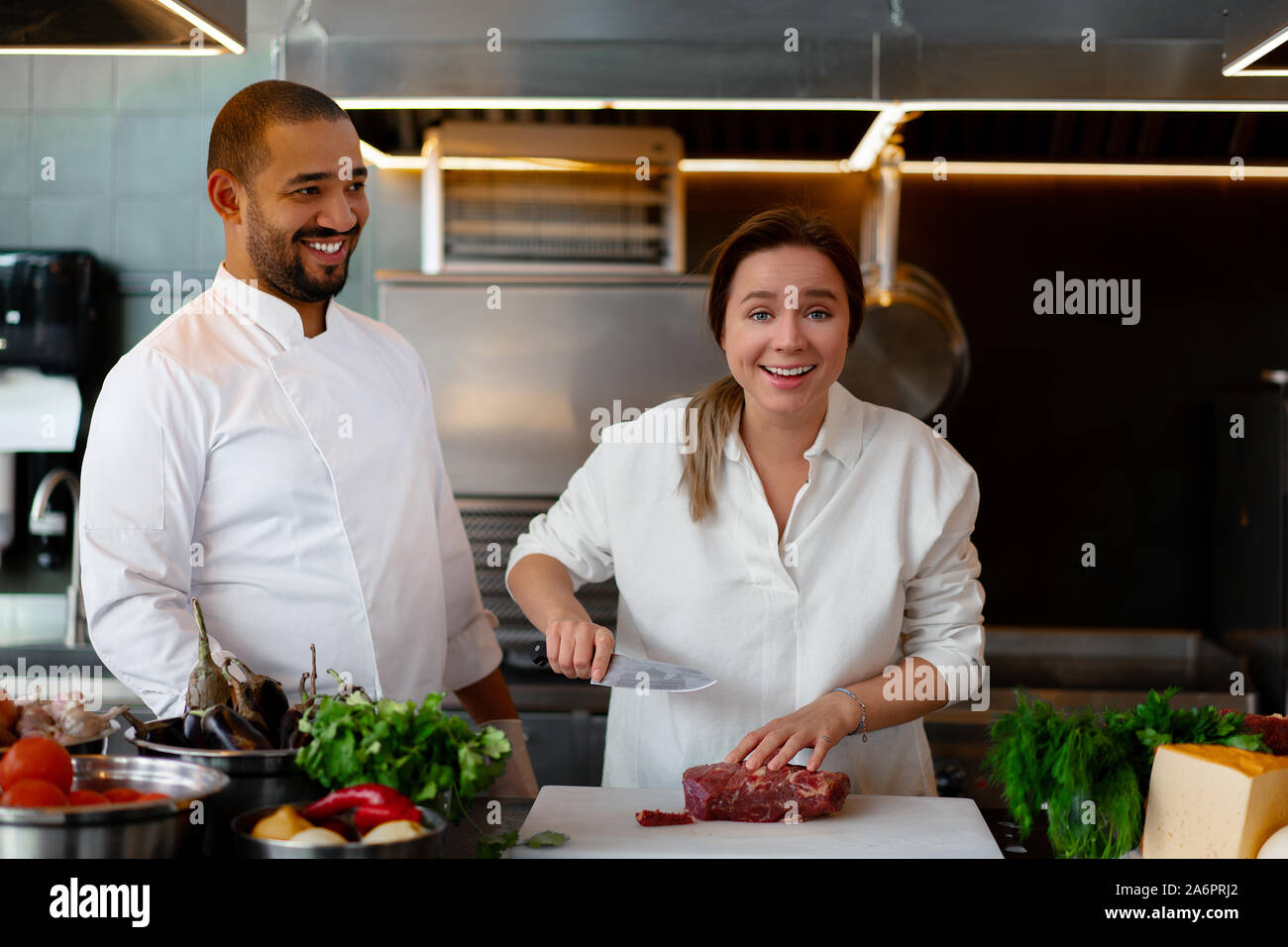 Handsome young African chef is cooking together with Caucasian girlfriend in the kitchen A cook teaches a girl how to cook. Man and woman cooking in p Stock Photo