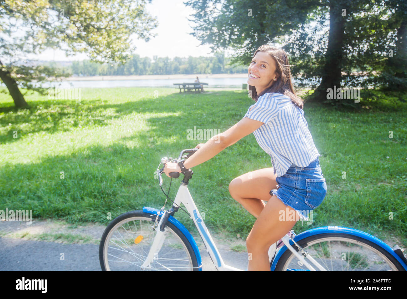 Relaxed young woman enjoying summer day with bicycle in nature. Beautiful girl outdoor portrait Stock Photo