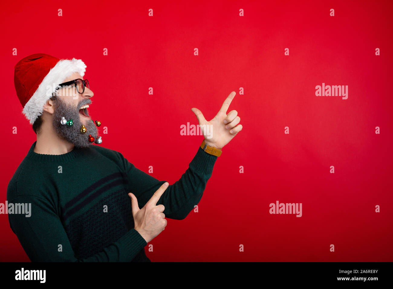 Photo of crazt man screaming and pointing at copyspace over red background and wearing santa claus hat Stock Photo