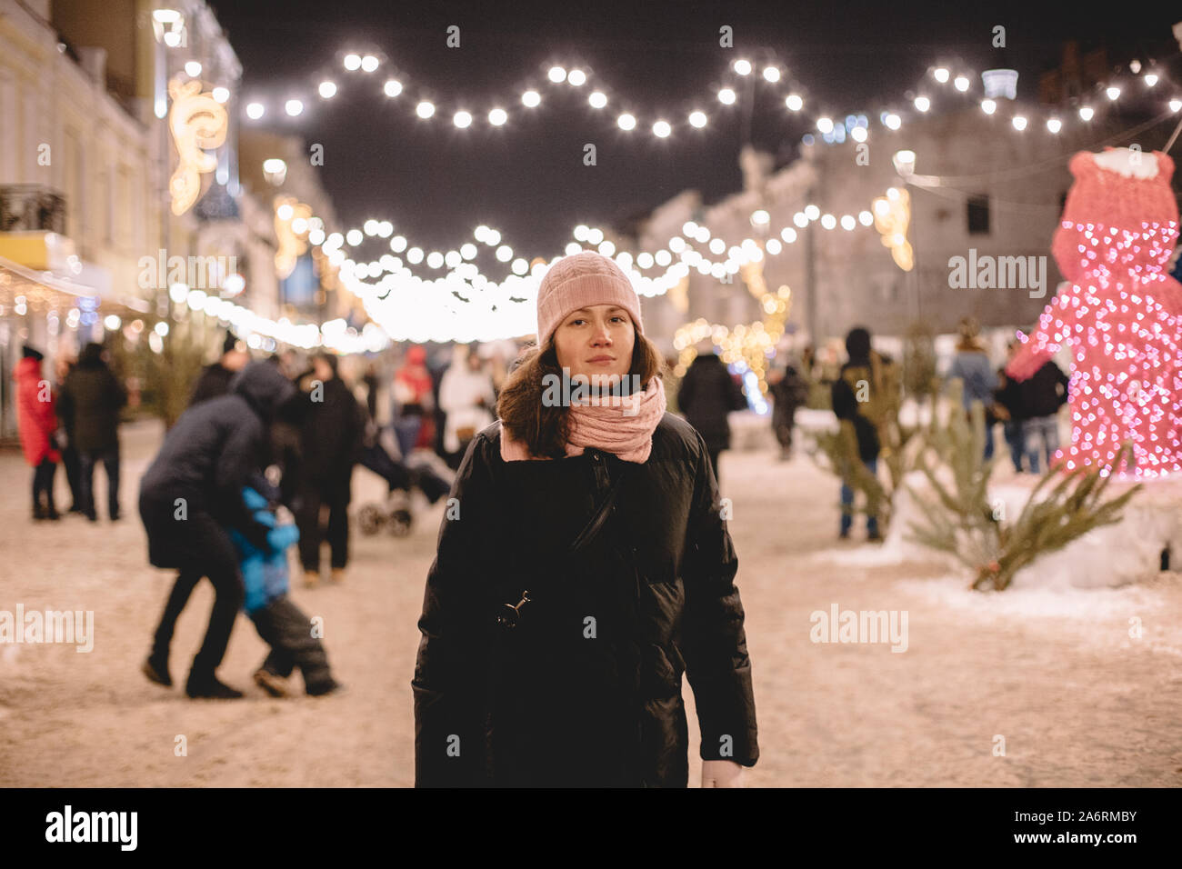 Young woman wearing warm clothing standing in brightly lit street Stock Photo