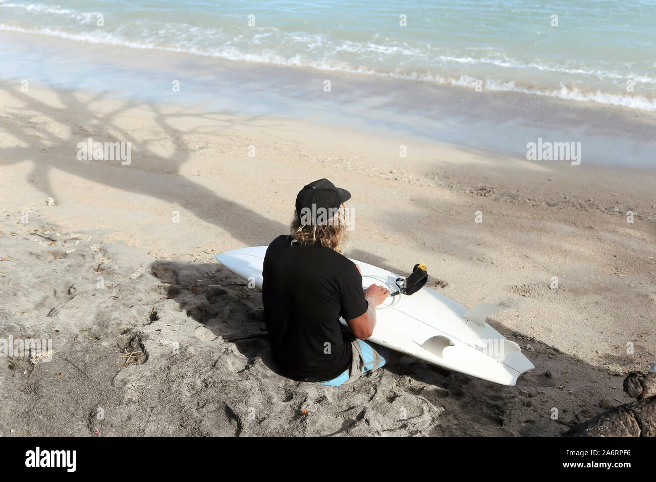 Title Surfer with surfboard at beach Stock Photo