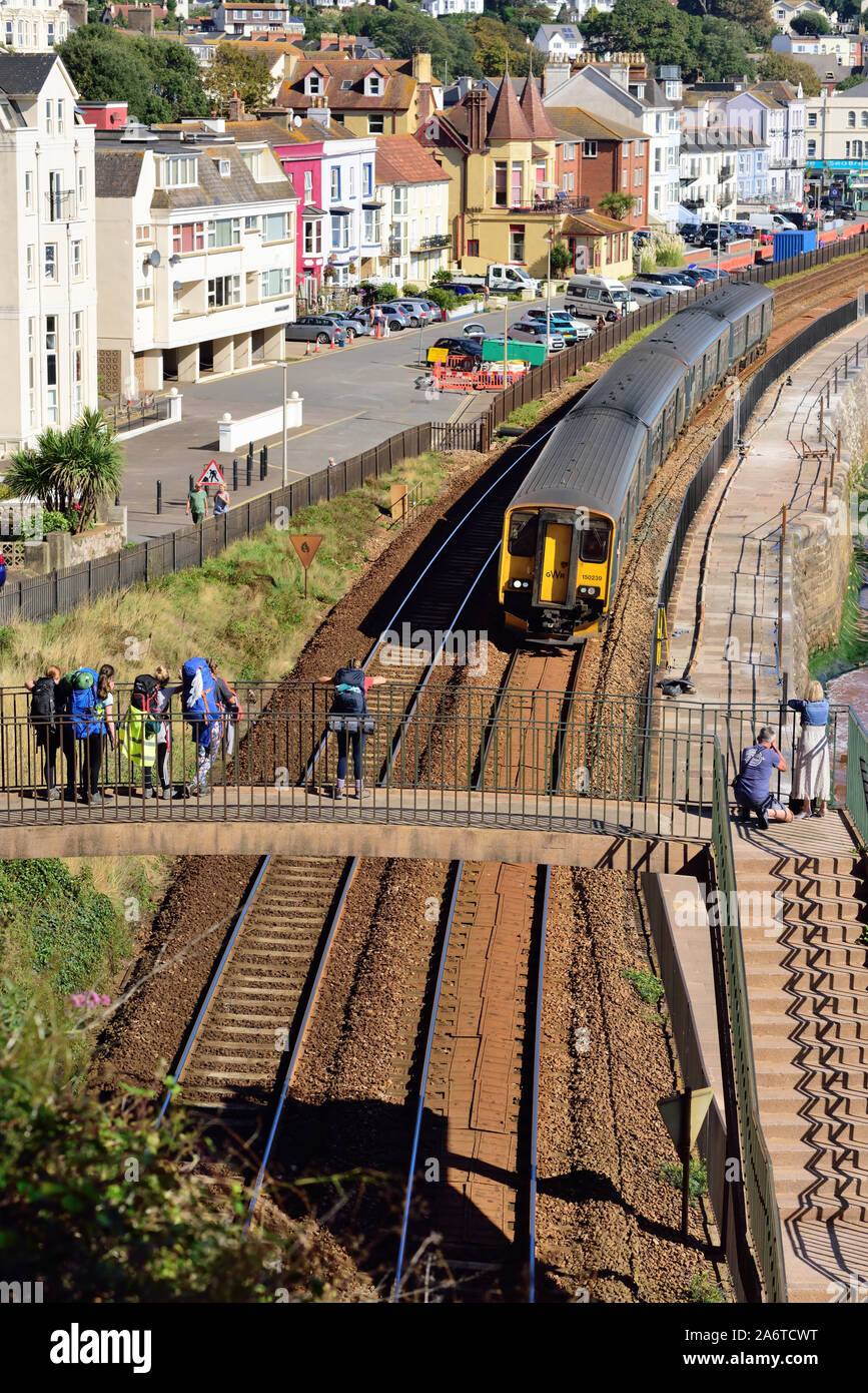 A diesel multiple unit heading for Paignton, passing along the sea wall at Dawlish. Stock Photo