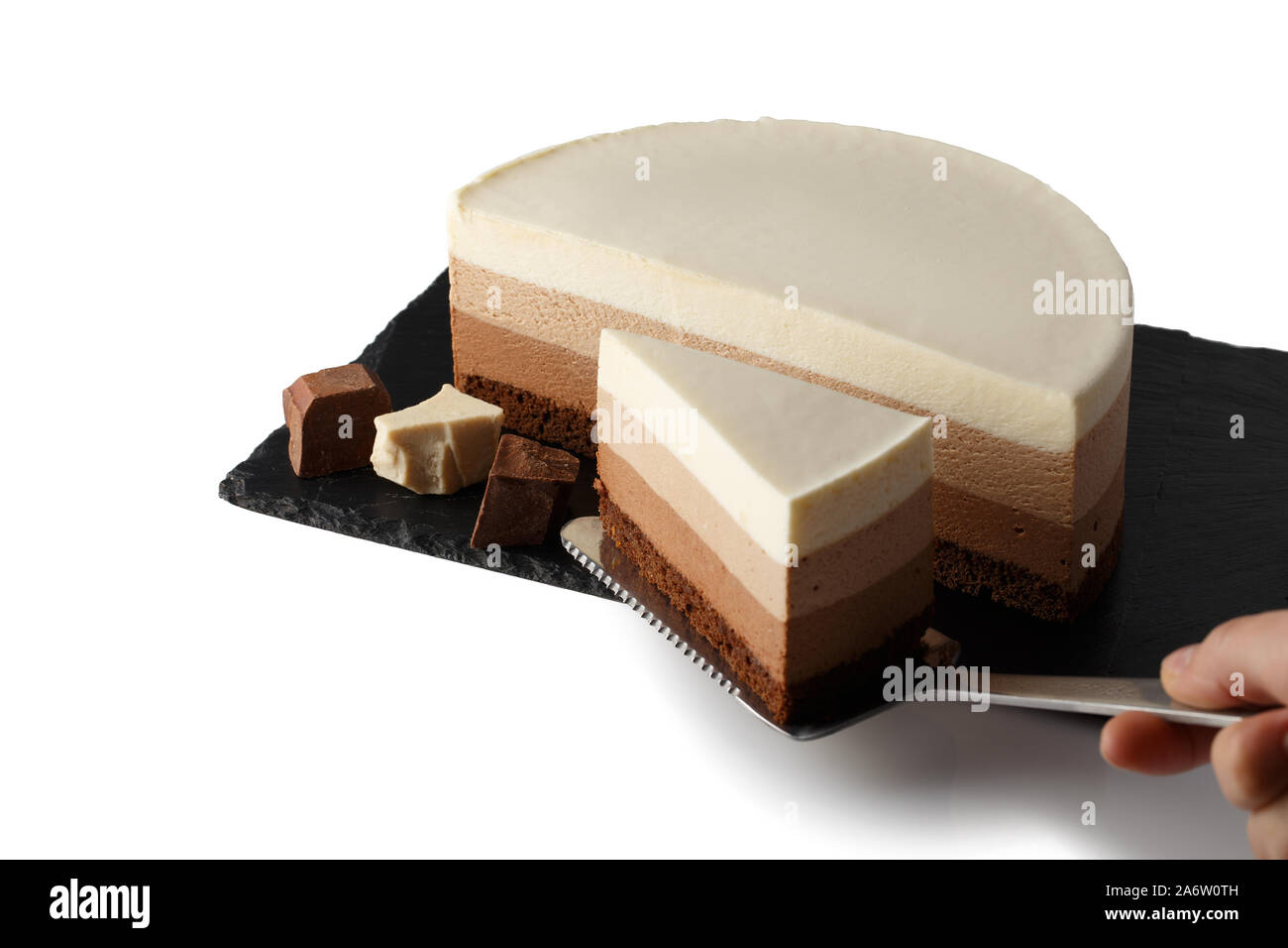 Delicious cake with three different kind of chocolate on plate of shale. Isolated on white background.  Cook picks up a cut piece of cake on a pastry Stock Photo