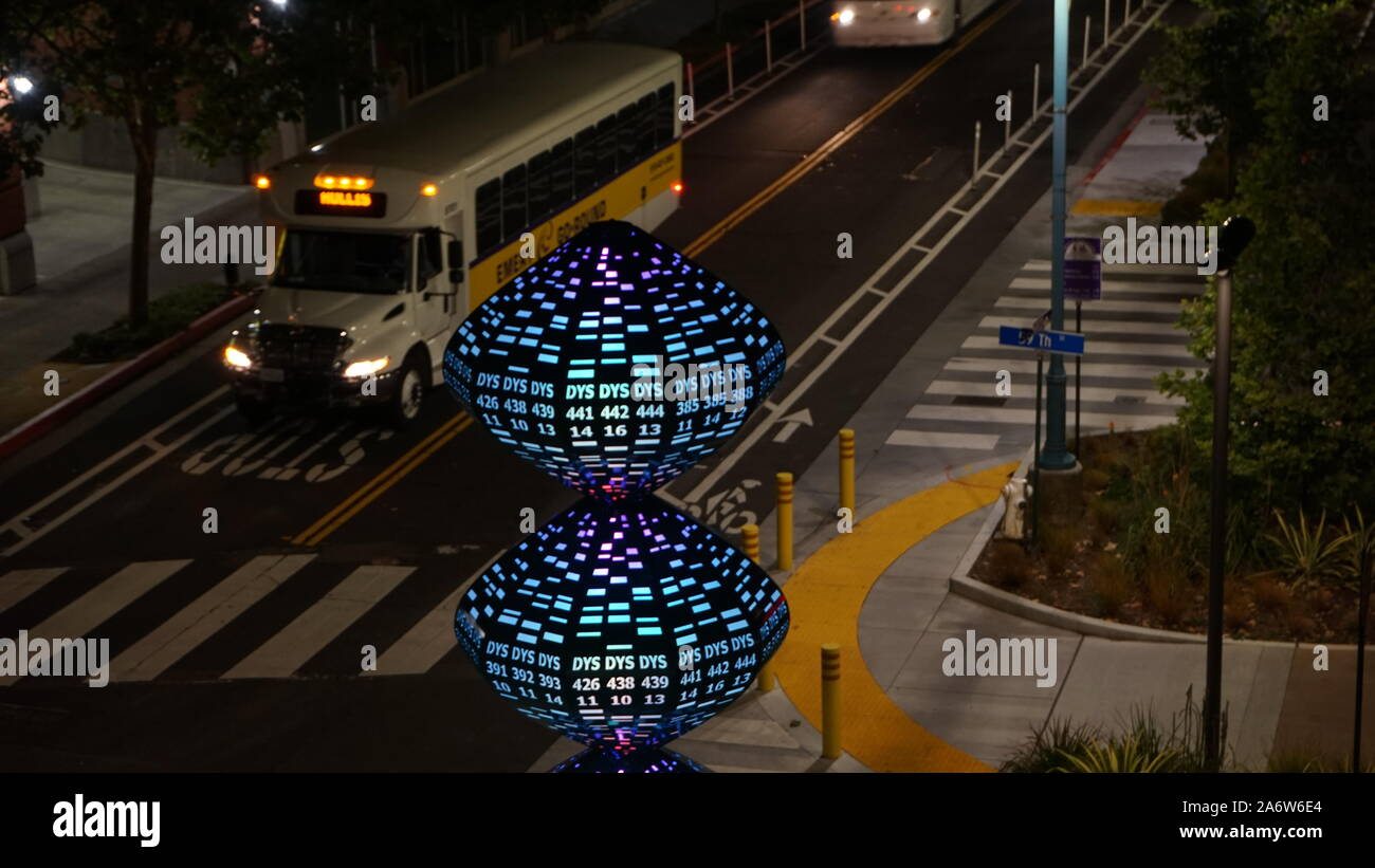 Lighted tech sculpture with numbers with Hollis Street Emery-Go-Round shuttle at night near Amtrak Station, Emeryville, California, USA Stock Photo