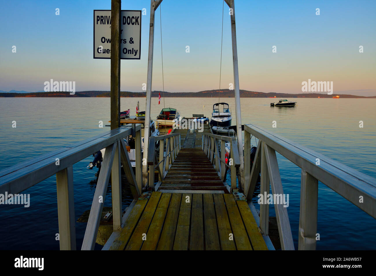 A boat dock jutting out into the Stewart Channel loaded with pleasure craft on a calm summer evening on Vancouver Island British Columbia Canada. Stock Photo