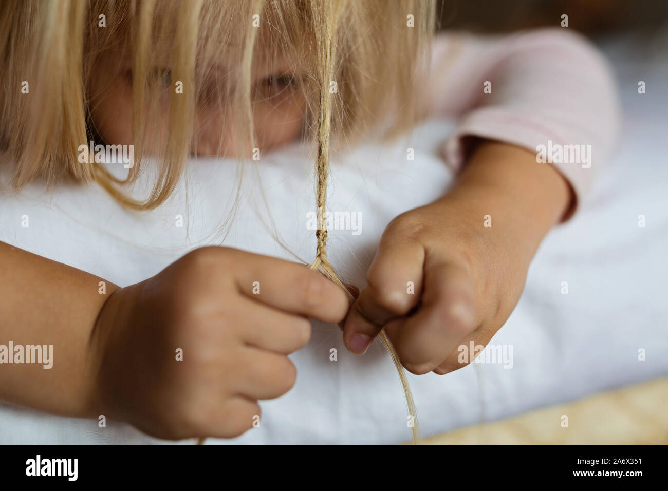 Cute blonde little girl in pajamas playing in white bed, early morning before going to kindergarten. Bedtime, playtime, relaxation concept Stock Photo