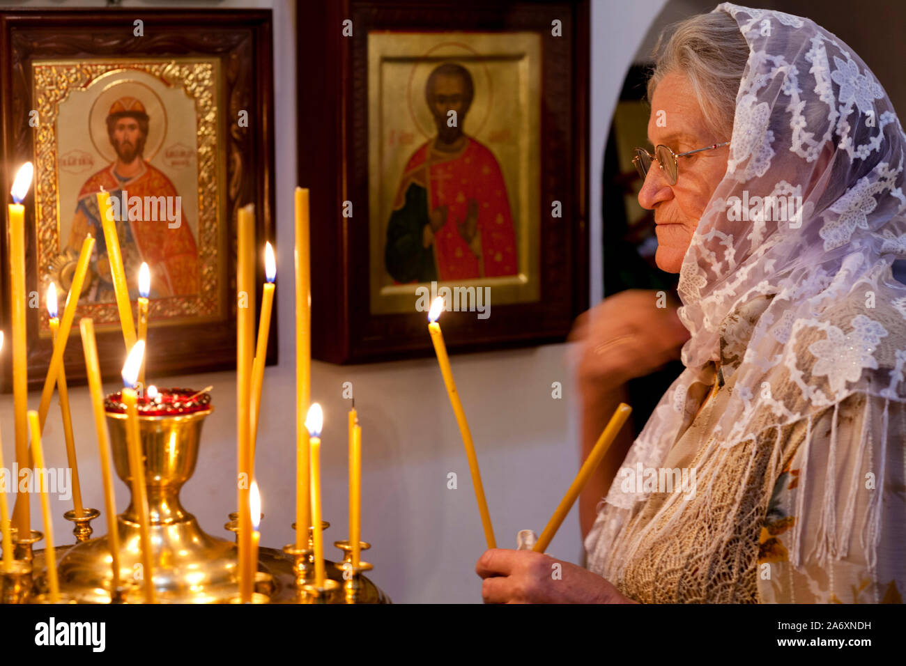 An elderly woman puts a candle near the iconostasis in the Temple of the Holy prophet of God Elijah, in Kitay-Gorod, on Elijah's day Stock Photo