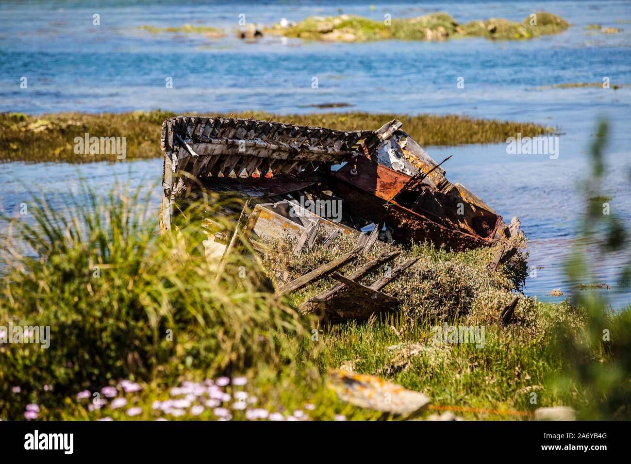 Ein altes Holzboot verrottet aan einem Strandstück in der Bretagne. Der Rückgang der kleinen Fischereibetriebe hinterläßt seine Spuren, seit die Meere Stock Photo