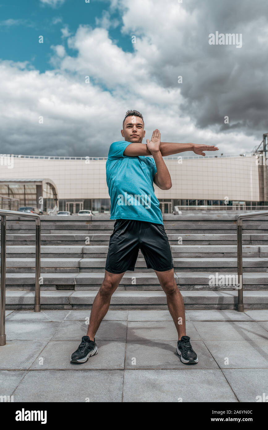 Athletic man, summer afternoon training in city, active lifestyle, modern fitness workout, sportswear t-shirt shorts sneakers. Warming up the muscles Stock Photo