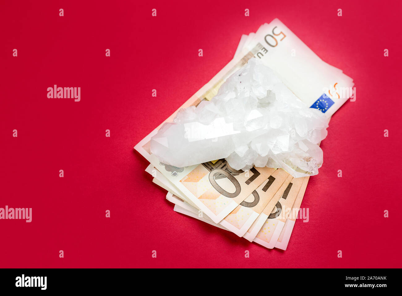 Lot of 50 euro bank notes under white pure crystal gemstone on red background. Conceptual image of business and finances in semi precious gemstone. Stock Photo