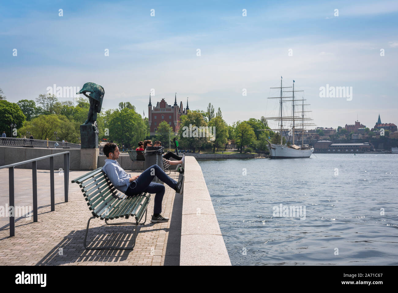 Stockholm waterfront, view in summer of a young man relaxing on a bench along the Blasieholmen waterfront in central Stockholm, Sweden. Stock Photo