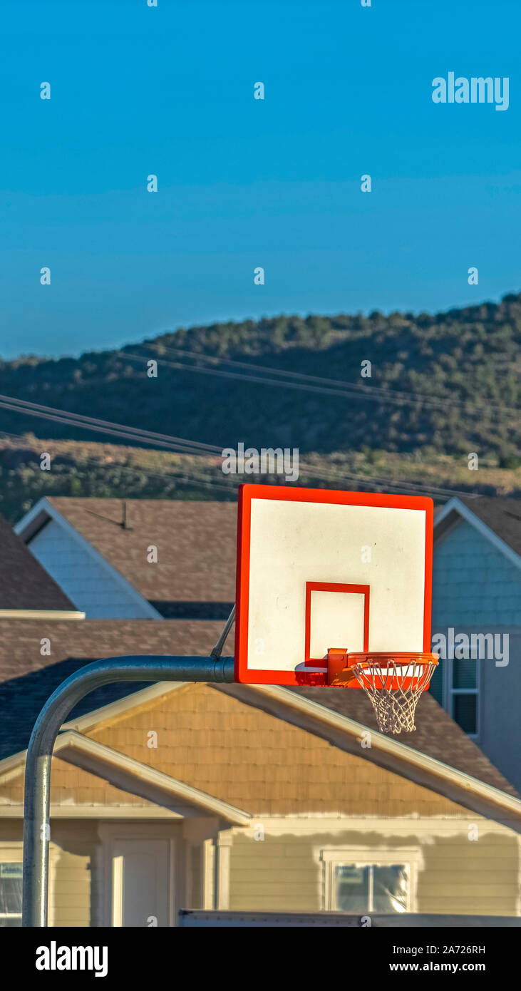 Vertical Focus On A Basketball Court With Homes And Mountain Background On A Sunny Day Stock Photo Alamy
