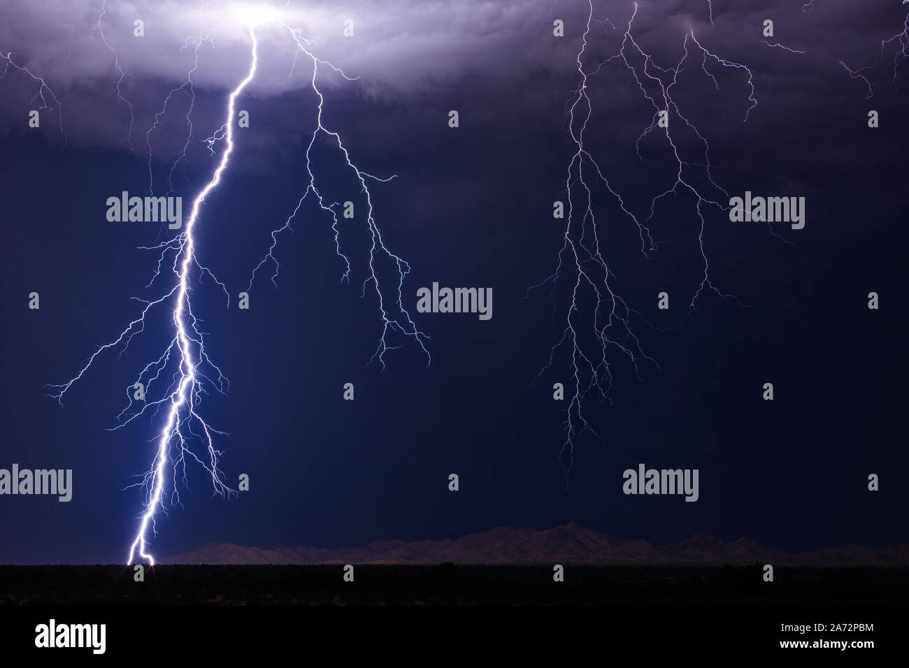 A powerful lightning bolt strikes from a thunderstorm in the Arizona desert near Gila Bend. Stock Photo
