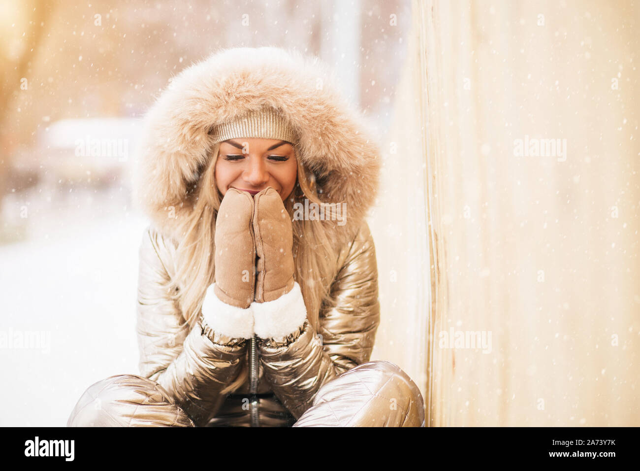 Lovely caucasian happy girl wearing golden jumpsuit posing sitting on snow, holding his palms together as if in prayer, smiling dreaming, enjoying tim Stock Photo
