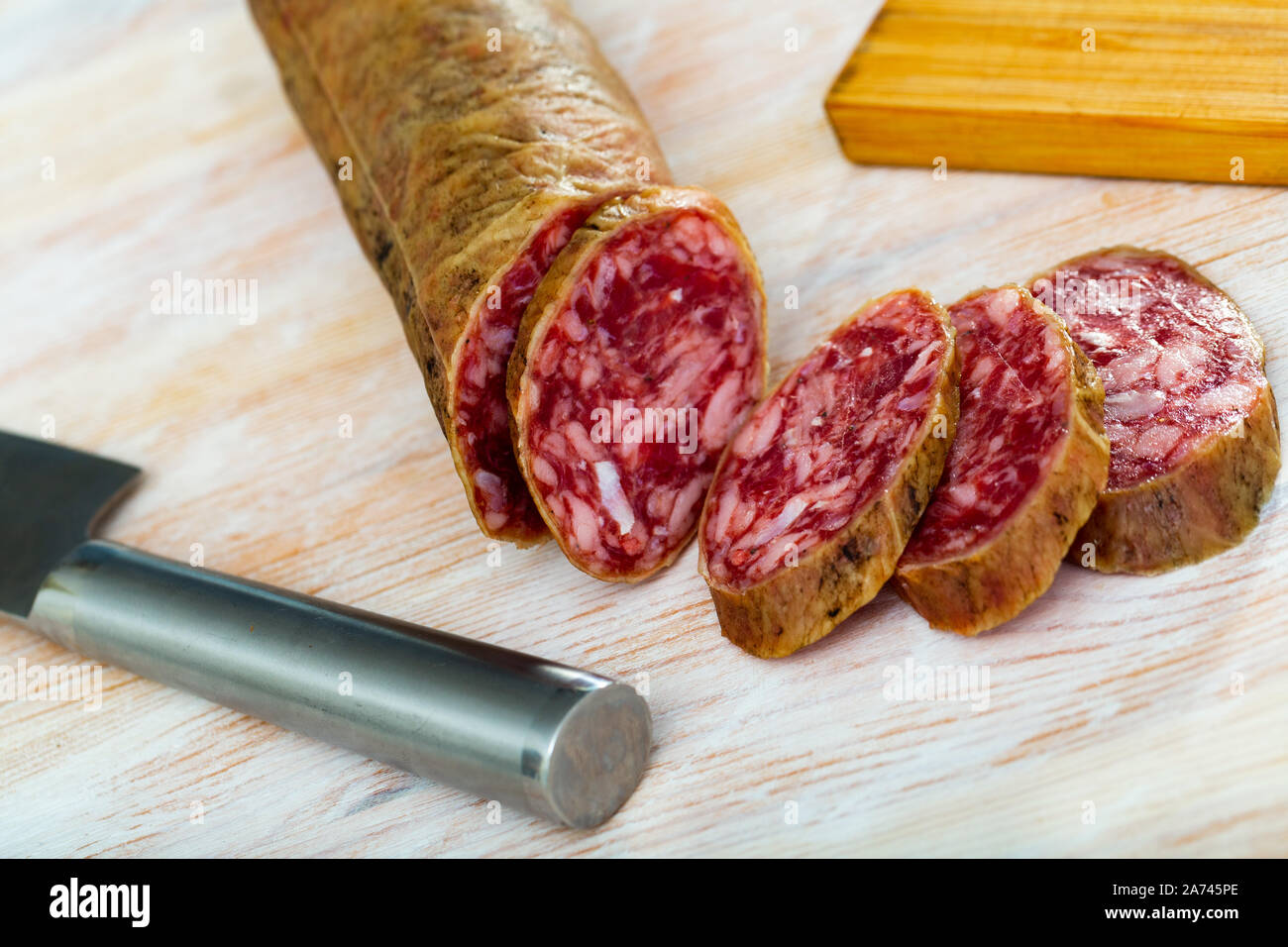 Thin salchichon sausage slices on wooden background, view from above Stock Photo