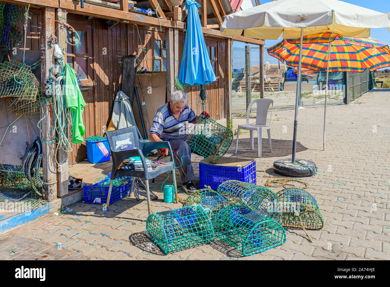 09.16.2019. Algarve, Portugal. Local fisherman repairing octopus traps, Santa Luzia, East Algarve Stock Photo