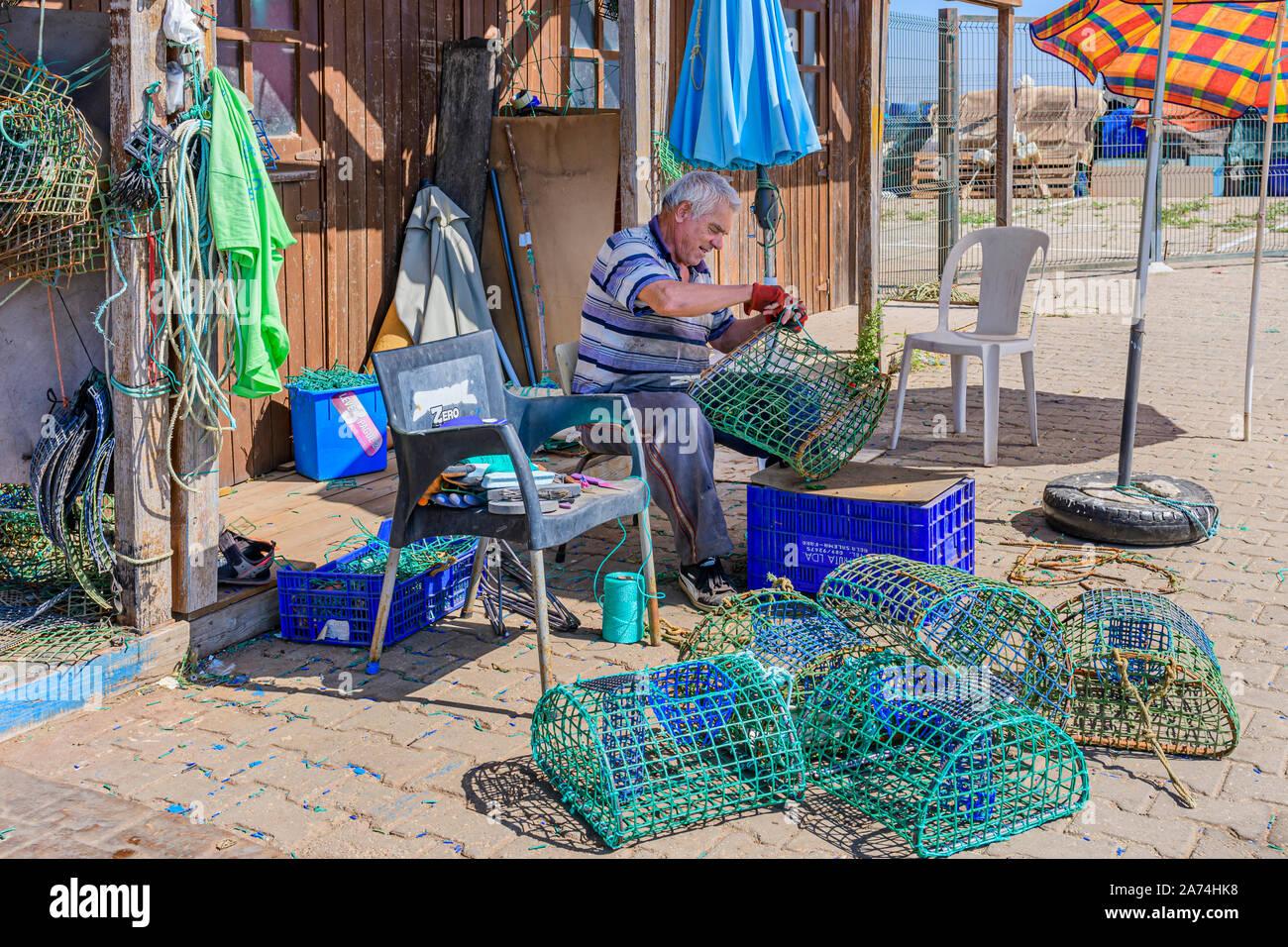 09.16.2019. Algarve, Portugal. Local fisherman repairing octopus traps, Santa Luzia, East Algarve Stock Photo