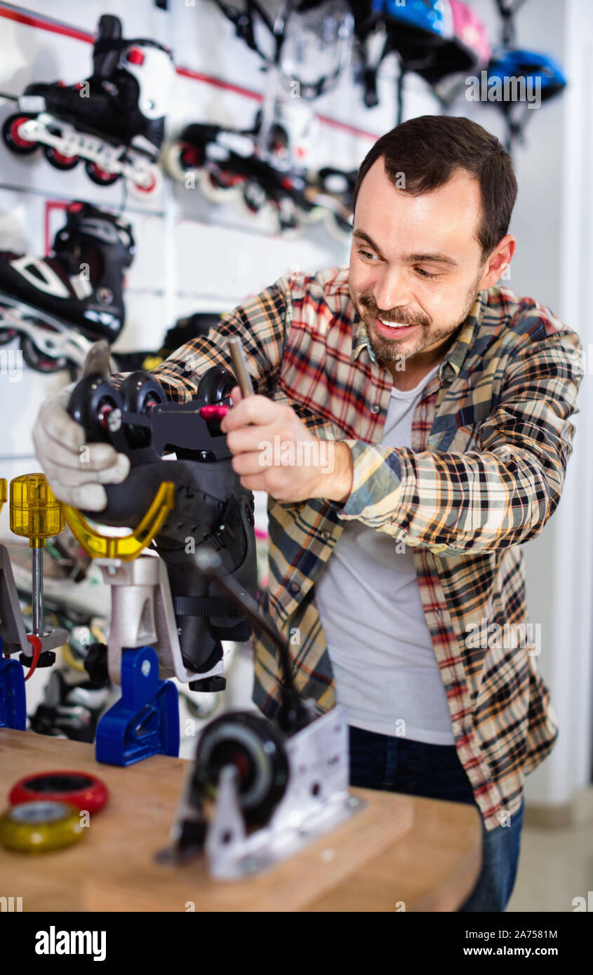 Young pleasant smiling male repairer fixing roller-skates in sports store Stock Photo