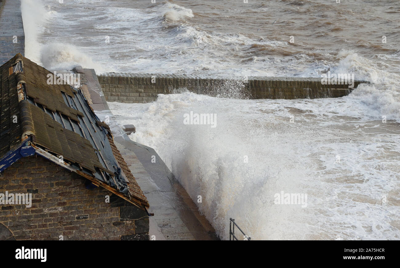Rough sea at Dawlish, and the storm damaged roof of a building beside the railway.. Stock Photo